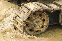 Lagarta velha do ferro na areia molhada Rodas e fita de aço oxidadas de uma grande escavadora, tanque da lagarta, máquina escavad imagem de stock