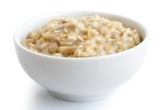 Lagat mat helt havregryn i den vita keramiska bunken som isoleras på whi Arkivfoton