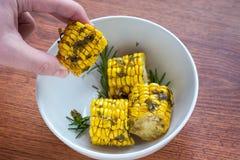 Lagat mat i ugnshavren med örter på en träbakgrund i den vita bunken som lagar mat havremajskolvar vid kockhanden, bästa sikt arkivbild