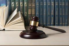 Lagbegreppet - boka med trädomareauktionsklubban på tabellen i en rättssal eller ett framtvingandekontor Arkivfoton