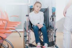Lagd in på sjukhus flicka på rullstolen arkivfoto