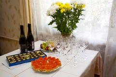 Lagd tabell med choklader, smörgåsar med kaviaren och exponeringsglas av champagne Arkivbilder