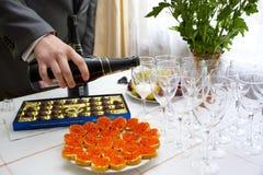 Lagd tabell med choklader, smörgåsar med kaviaren och exponeringsglas av champagne Arkivfoton