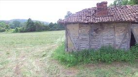 Lage antenne naast het oude en verlaten huis in de weide stock video