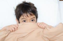 Lage des kleinen Jungen auf Bett mit halbem Gesicht der umfassenden Abdeckung Stockfotografie