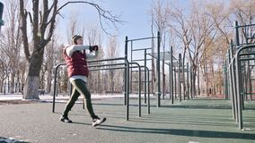 Lage hoek tegen de zon Het sportenmeisje in de winter op de speelplaats maakt uitvalt vooruit het striding stock footage