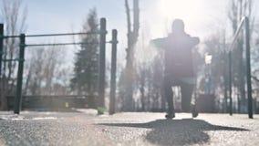 Lage hoek tegen de zon Het sportenmeisje in de winter op de speelplaats maakt uitvalt vooruit het striding stock video