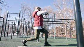 Lage hoek tegen de zon Het sportenmeisje in de winter op de speelplaats maakt uitvalt vooruit het striding stock videobeelden