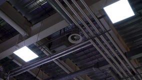 Lage hoek van metaalpijpen van hvacsysteem en lampen opgezet aan plafond van grote wandelgalerij stock videobeelden