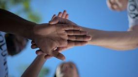 Lage hoek van positieve vrijwilligers die handen samen houden