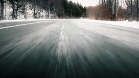 Lage hoekmening: Auto het drijven snel door bevroren bosweg stock video