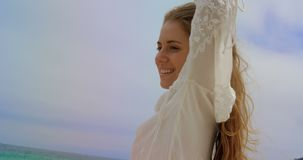 Lage hoekmening van Gelukkige Kaukasische vrouw status op het strand 4k stock videobeelden