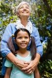 Lage hoekmening van glimlachende grootmoeder en kleindochter die zich tegen bomen bevinden royalty-vrije stock fotografie