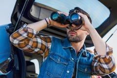 lage hoekmening van het mannelijke toerist kijken door verrekijkers terwijl zijn meisje royalty-vrije stock foto
