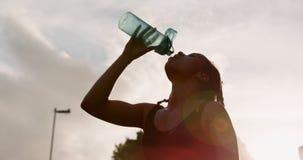 Lage hoekmening van jong Afrikaans Amerikaans vrouwen drinkwater in de stad 4k stock videobeelden