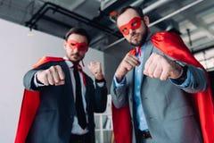 lage hoekmening van knappe super zakenlieden in maskers en kaap die vuisten tonen stock fotografie