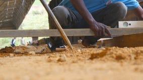 Lage hoekmening van onherkenbare Indische mannelijke handen die niveaus controleren nauwkeurigheid tijdens de bouw houten vloer l stock video