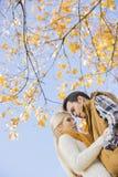Lage hoekmening van paar die tegen de herfstboom koesteren Stock Afbeeldingen