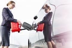 Lage hoekmening van stafmedewerker met bus die auto van brandstof voorzien tegen hemel royalty-vrije stock foto's