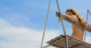 Lage hoekmening van vrouwenzitting op observatietoren op het strand 4k stock video