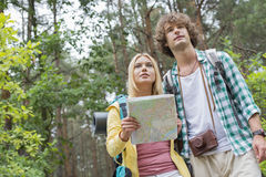 Lage hoekmening van wandelend paar met kaart in bos royalty-vrije stock foto's