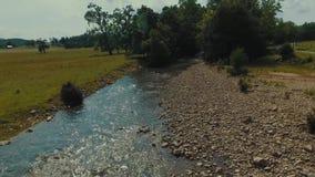 Lage hommelluchtparade van een stroom van het land naast een landbouwbedrijf in centraal Virginia stock footage