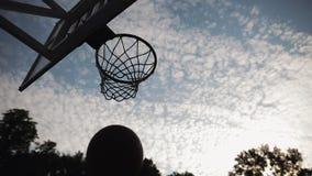 Lage invalshoek van basketbalhoepel en mannetjes gooien en unscoring op gedeeltelijk troebele avondachtergrond Gezonde stock video