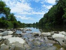 Lage mening van de zomerrivier die op rivierrotsen lopen met blauwe hemel Royalty-vrije Stock Afbeelding