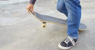 Lage sectie die van de jonge mens zijn schoenveter binden terwijl het buigen op skateboard in skateboardpark 4k stock videobeelden
