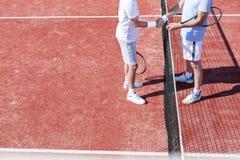 Lage sectie mensen die handen schudden terwijl status door tennis netto op rood hof tijdens gelijke royalty-vrije stock foto