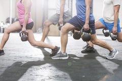 Lage sectie mensen die kettlebells bij crossfitgymnastiek opheffen Stock Foto