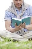 Lage sectie van het boek van de jonge mensenlezing op gras Stock Foto's