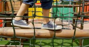 Lage sectie van mengen-rasschoolmeisje het spelen in schoolspeelplaats op een zonnige dag 4k stock footage