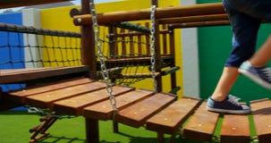 Lage sectie van mengen-rasschoolmeisje het spelen in schoolspeelplaats op een zonnige dag 4k stock videobeelden
