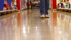 Lage sectie van vrouw het lopen met het winkelen mand stock footage
