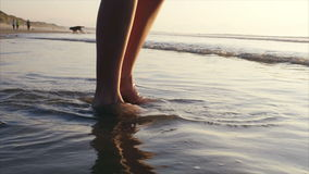 Lage sectie van vrouw het spelen met golven die op kust breken stock videobeelden