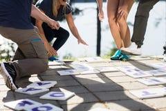 Lage Sectie van Zaken Team Solving Crossword stock foto's