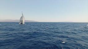 Lage vlucht voorbij een jacht op zee stock footage