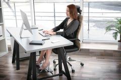 Lagekonzept Junge Frau, die mit c-omputer im Büro arbeitet Lizenzfreie Stockfotos