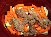Lagen van gesneden witte aardappels en wortelen en gebruind het stoven rundvlees in een langzaam kooktoestel stock foto's