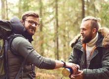 Lager-, Abenteuer-, Reisen und Freundschaftskonzept Mann mit einem Rucksack und einem Bart und sein Freund, der im Wald wandert Stockfoto