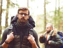 Lager-, Abenteuer-, Reisen und Freundschaftskonzept Mann mit einem Rucksack und einem Bart und sein Freund, der im Wald wandert Lizenzfreie Stockbilder