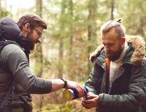 Lager-, Abenteuer-, Reisen und Freundschaftskonzept Mann mit einem Rucksack und einem Bart und sein Freund, der im Wald wandert Lizenzfreies Stockbild