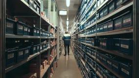 Lager-Arbeitskraft, die nach Produkten auf Regalen sucht Großhandels-, logistisches, Versand-und Leute-Konzept stock footage