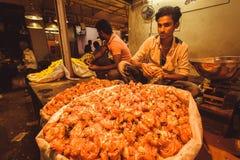 Lager av blommor och den olyckliga representanten av den indiska marknaden Arkivbilder