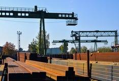 Lager av metallprodukter, metall, på bakgrunden av en lastningsbryggakran på en industriell plats arkivfoto