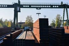 Lager av metallprodukter, metall, på bakgrunden av en lastningsbryggakran på en industriell plats royaltyfri fotografi