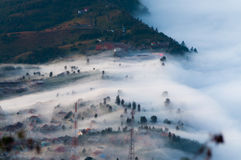 Lager av mist över bergen och i en by Arkivbilder