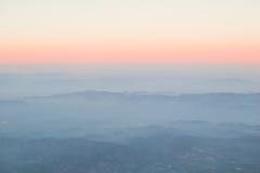 Lager av molndimmaberg och soluppgång Arkivbild
