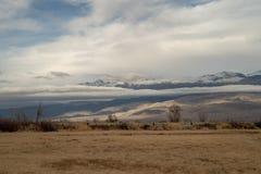 Lager av vita moln och snöig bergmaxima fotografering för bildbyråer